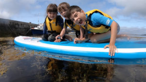 Kids having fun stand up paddleboarding in Clare